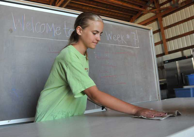 by: PAMPLIN MEDIA GROUP: VERN UYETAKE - Madison Roel, an incoming freshman, prepares the table before student interns begin laying out CSA shares for pickup on July 11.