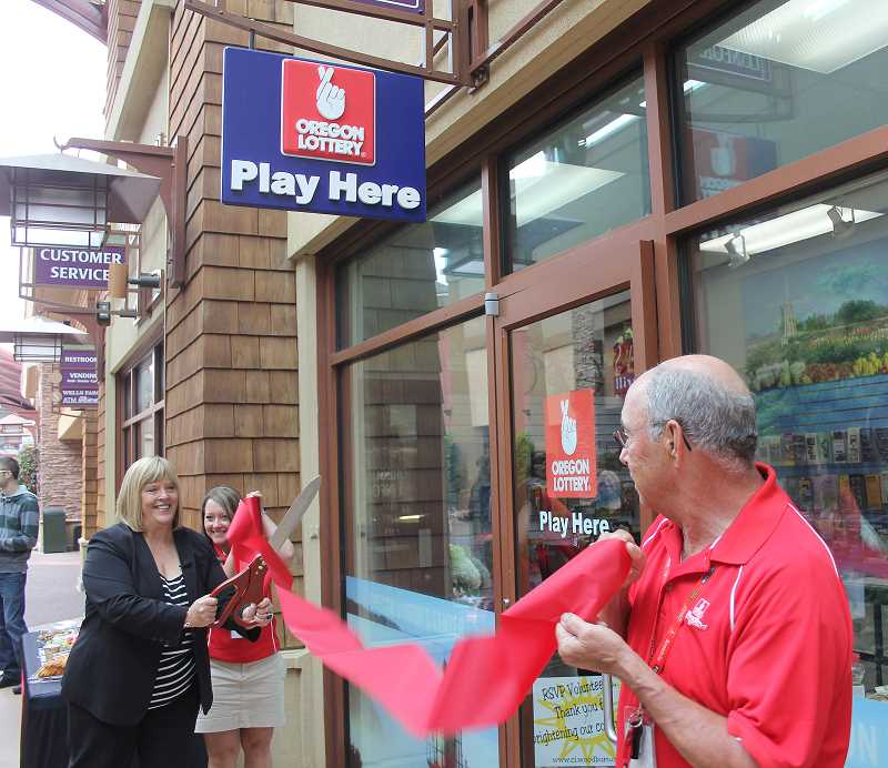 by: BY JEFF MCDONALD - Stacy Shaw of the Oregon Lottery cuts the ribbon at the grand opening ceremony last week at the Woodburn Premium Outlets. The Oregon Lottery opened a new kiosk in a shared space with the Woodburn Visitor and Information Center.
