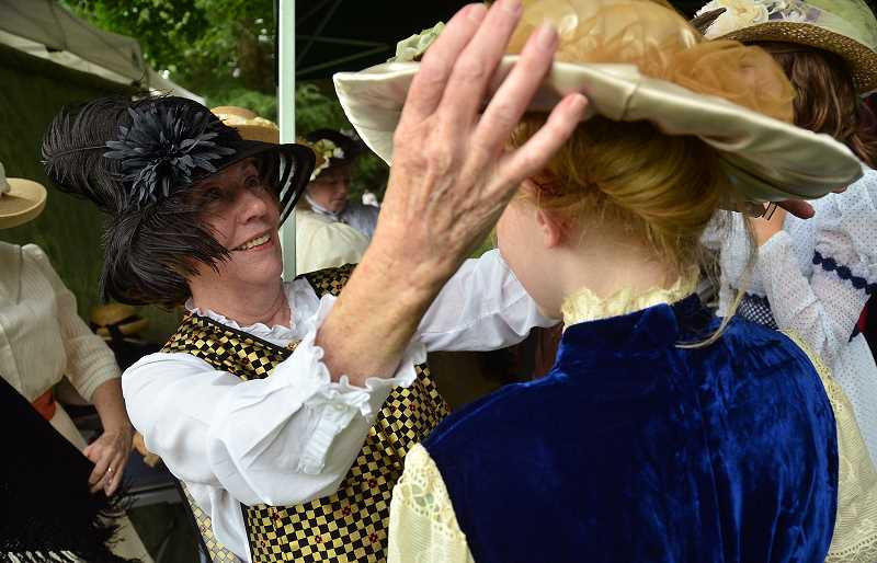 by: VERN UYETAKE - Darlene Schwartz adjusts Ashley Newbore's hat for an old time photo.