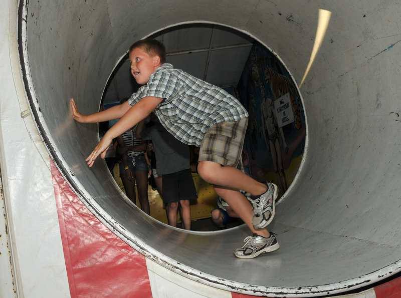 by: VERN UYETAKE - A boy gets spinning at the fun house at the Old Time Fair.