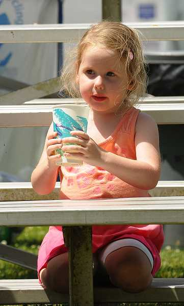 by: VERN UYETAKE - A girl cools off at the Old Time Fair.