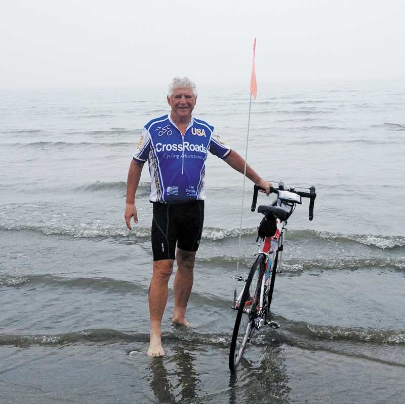 by: SUBMITTED - Bill MacKenzie dips his bikes front wheel in the Atlantic Ocean near Boston on June 28 after he reached the end of his cross-country bike ride.
