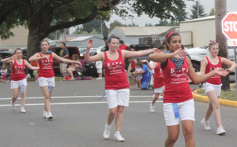 by: BY JEFF MCDONALD  - Dancers from Karla's Academy of Performing Arts of Molalla perform as part of the festival's parade on Third Street. The parades theme was 'Celebrating our Veterans,' with a group of veterans serving as grand marshal and a number of entries who were dressed in red, white and blue.