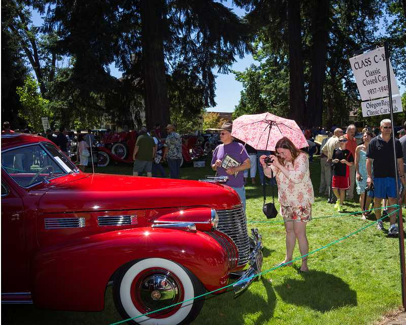 by: NEWS-TIMES PHOTOS: CHASE ALLGOOD - Below, a show attendee snaps a photo of one of the 300 autos that caught her eye during the one-day event.