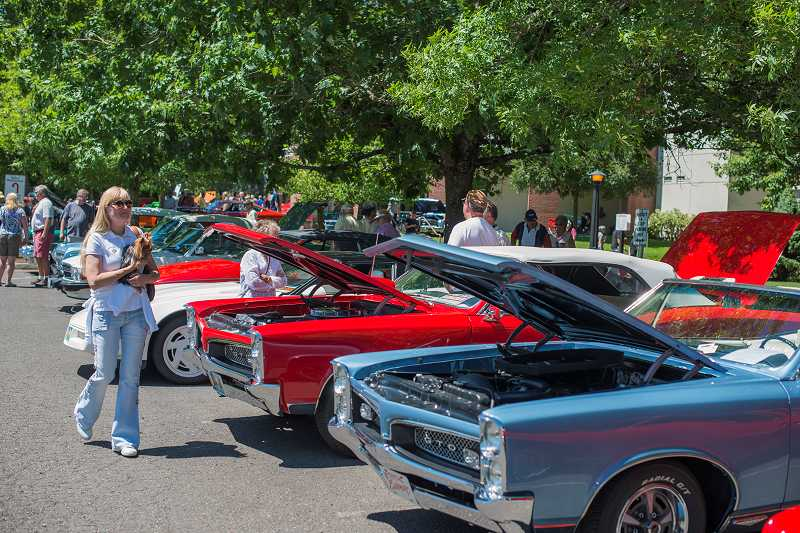 by: NEWS-TIMES PHOTO: CHASE ALLGOOD - Perusing merchandise on the Concours dElegance-hosted used car lot was a popular activity during the all-day show Sunday. This years Concours drew a large crowd to Pacific University in Forest Grove.