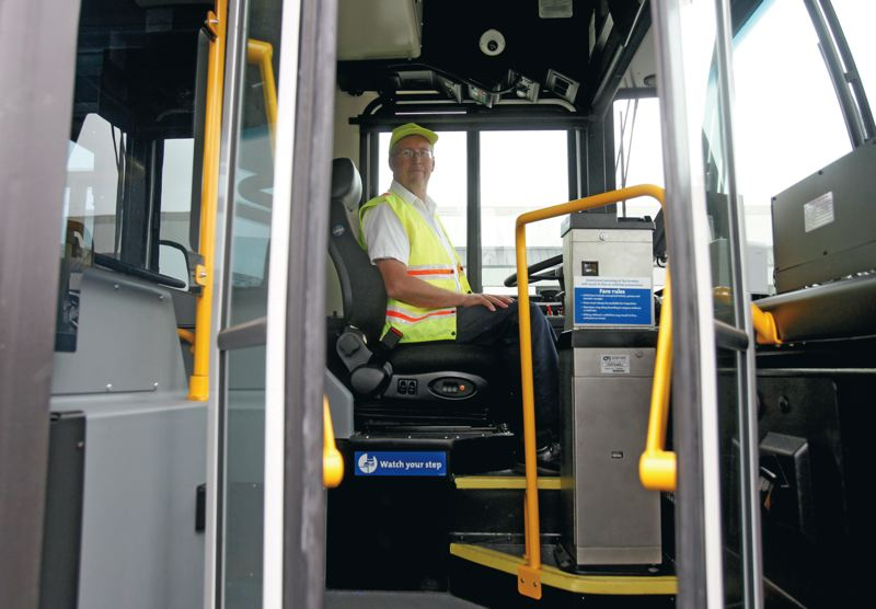 by: TIMES PHOTO: JONATHAN HOUSE - TriMet training supervisor Ken Jenson notes the adjustable drivers seat in the new generation of buses that TriMet showed off on Monday.