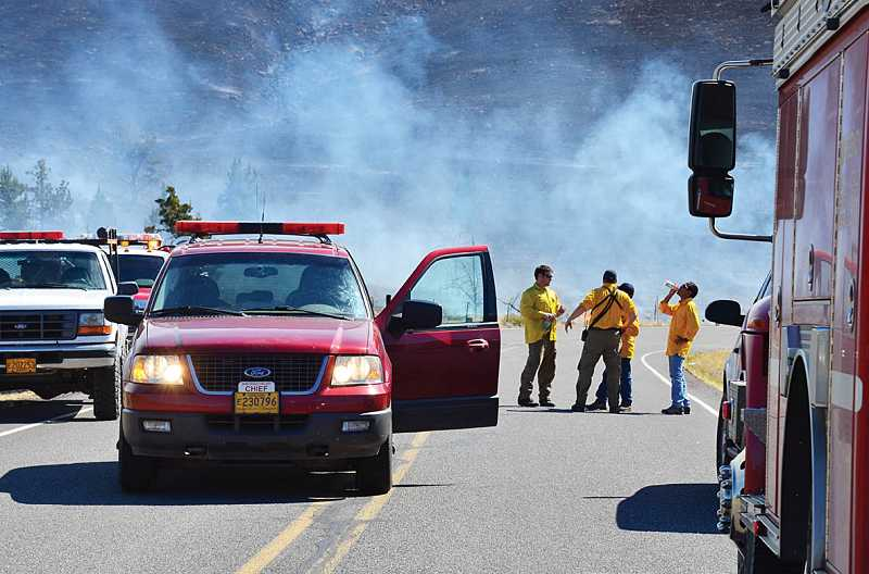 by: PHOTO BY LINDA LARSON - Warm Springs Fire and Safety Chief Dan Martinez, center, meets with a crew near the Wolfe Point subdivision.