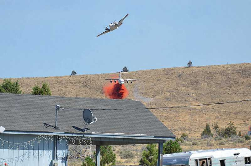 by: PHOTO BY LINDA LARSON - A small lead plane directs a large retardant jet dropping its load near a house in the Wolfe Point subdivision on the Warm Springs Reservation. The Sunnyside Turnoff Fire started Sunday morning and had grown to 45,491 acres by Wednesday.