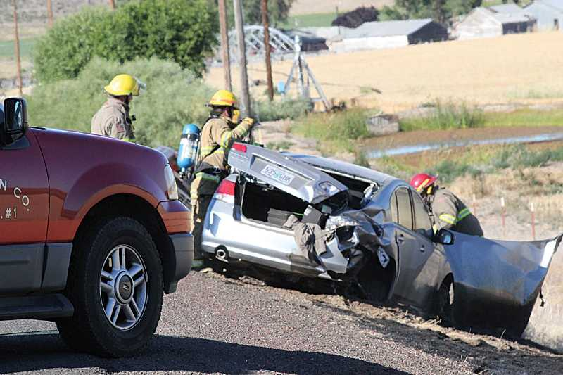 by: HOLLY M. GILL - Firefighters examine the Subaru driven by Chester Ward, 91, who died in a crash 