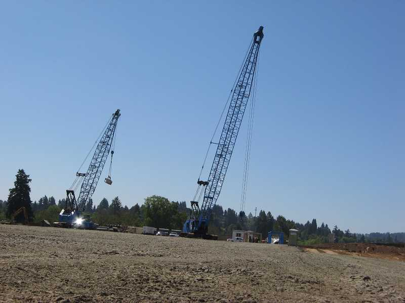 by: RAY PITZ - GOING UP - These cranes will help with the preliminary site work at the future Walmart store set to open in 2014.