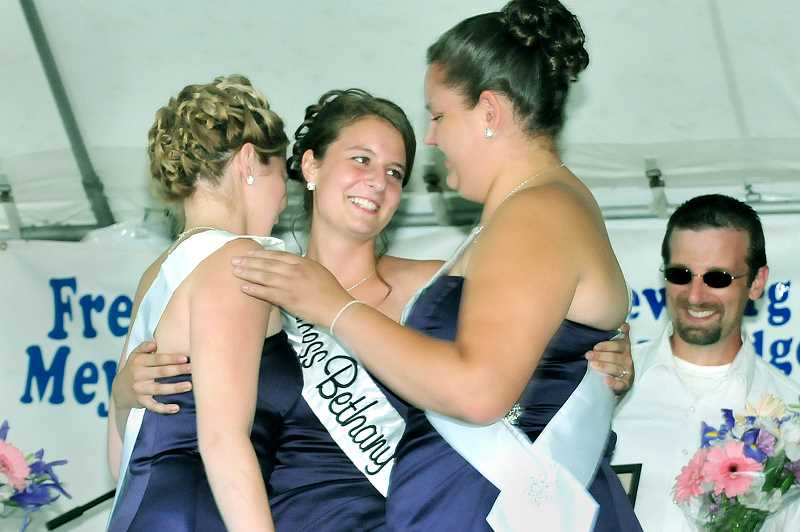by: GARY ALLEN - Newly-crowned Old Fashioned Festival Queen Bethany Geisch receives congratulatory hugs from the other two members of the court, Evie Rice and Lindsey Doran, on the main stage at Memorial Park.