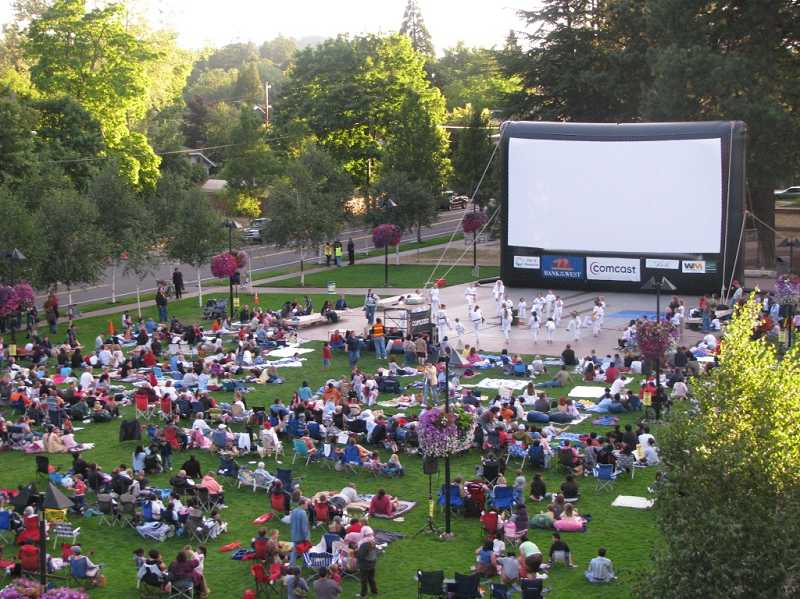 by: SUBMITTED PHOTO - Family and friends gather to enjoy entertainment and a movie during last year's Flicks by the Fountain. Movies will be shown in Beaverton City Park Friday nights this month, beginning this week.