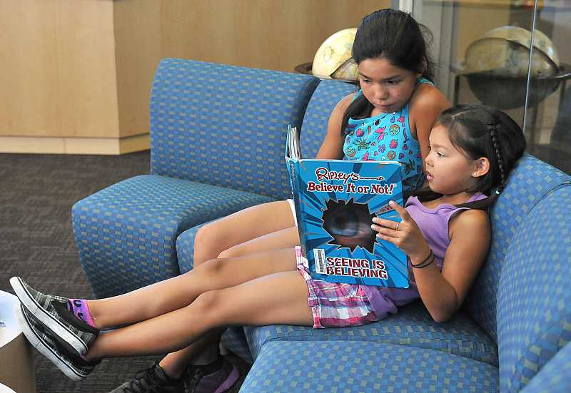 by: PAMPLIN MEDIA GROUP: VERN UYETAKE - Mia Carroll, 10, shares a book with her sister, Ava, 8, at Lowrie on July 10.