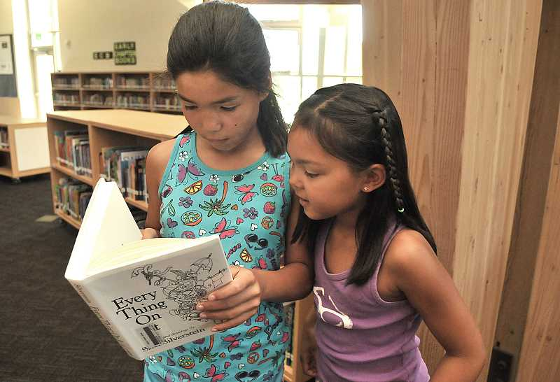 by: PAMPLIN MEDIA GROUP: VERN UYETAKE - Mia Carroll, 10, and her sister, Ava, 8, found some good books to read at Lowrie on July 10.