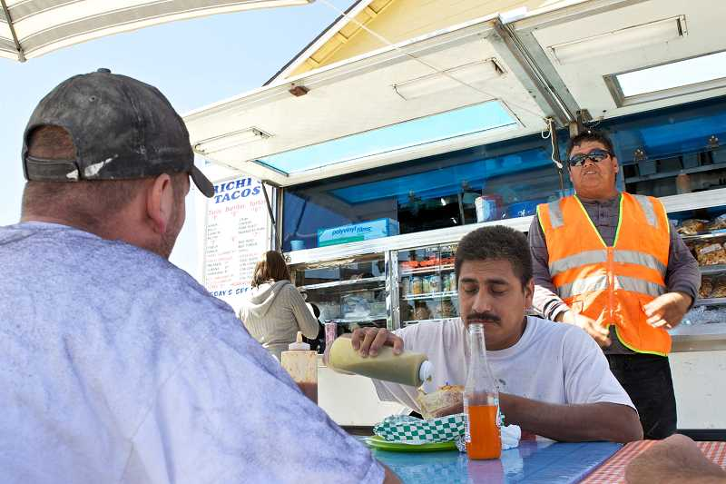 by: TIMES PHOTO: JAIME VALDEZ - James Jones, Guillermo Rosales and Juan Fonseca eat lunch at Richi's Tacos food cart located next to the Royal Manor Apartments along Southwest Lombard Avenue.