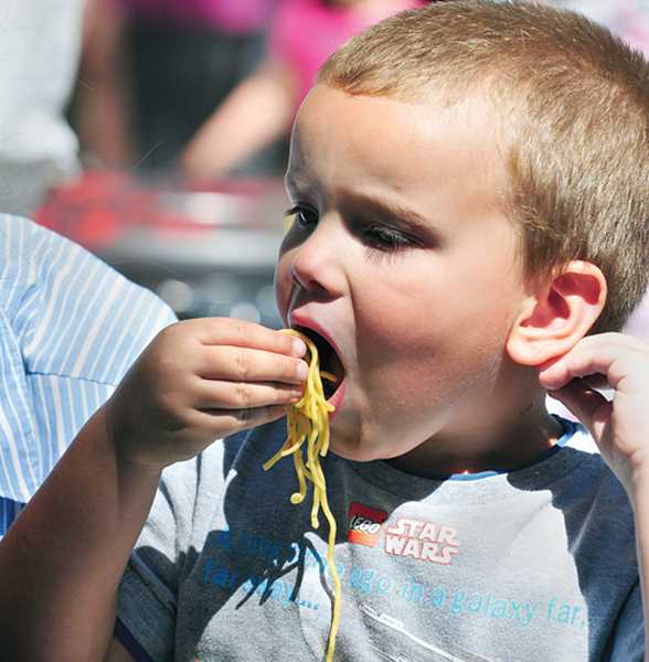 by: GARY ALLEN - Andrew Parlette enjoys some noodles in the midway of the festival in Memorial Park.