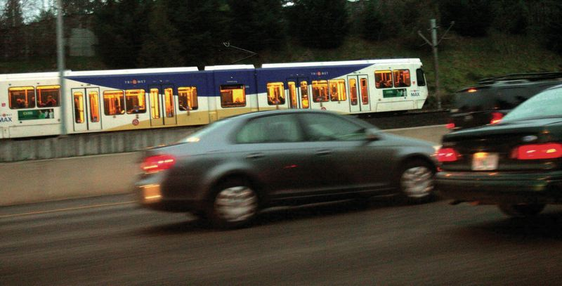 by: TRIBUNE PHOTO: JAIME VALDEZ - Tri-Mets light rail races past stop-and-go eastbound motorists along the Sunset Highway. Opponents in Tigard are gathering petition signatures to force a vote on transit proposals.