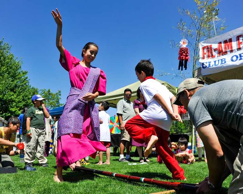 by: SUBMITTED PHOTO: JOHN LARIVIERE - Courtney Saqueton, 12, and her brother Ryan, 10, perform a Filipino bamboo pole dance in front of the Filipino American Club of Oregon booth at the Beaverton International Celebration.