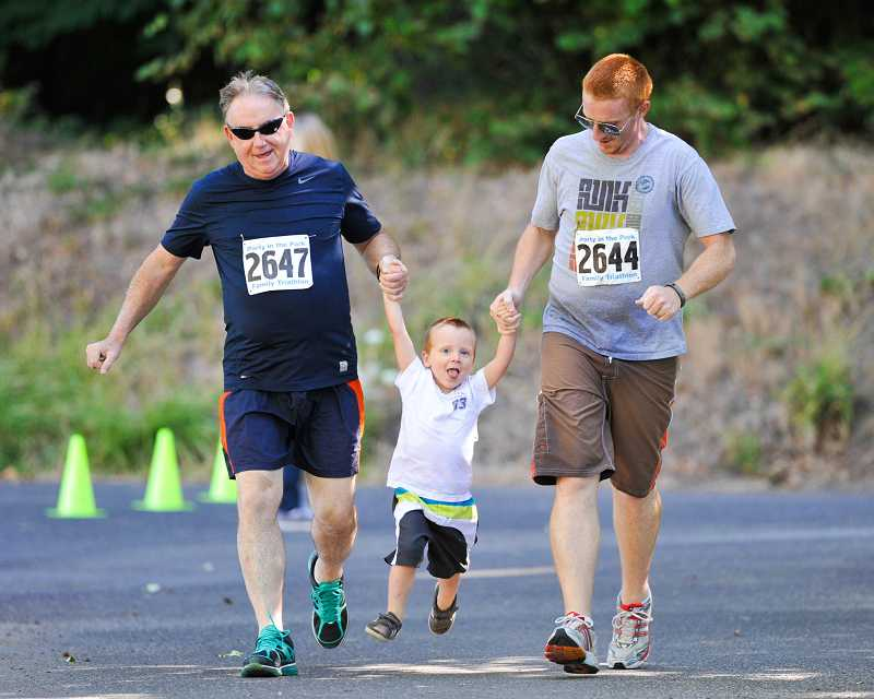 by: SUBMITTED PHOTO: JOHN LARIVIERE - Reece Nelson, 2, gets help finishing the running portion of the Family Triathlon from his father Tyler (right) and Grandpa Bob (left).