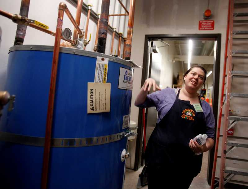 by: TIMES PHOTO: JONATHAN HOUSE - Natural Grocers store manager Krysti Weddle shows off the store's special heater that captures gases from the refigeration unit and turns them into heat for its water.