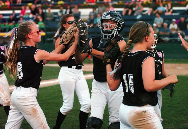 by: DAN BROOD - STAYING STRONG -- Members of the Tualatin City softball team celebrate with catcher Ella Hillier after she threw out a runner on a stolen base attempt in the District 4 title game.