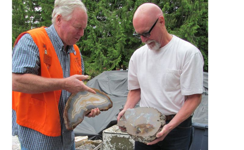 by: PHOTO BY ELLEN SPITALERI - Art Hess, left, points out the markings on a polished Brazilian agate, while David Hanna displays the innards of a huge thunder egg.