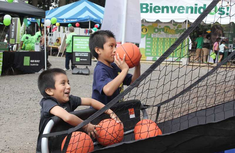 by: LINDSAY KEEFER - Two boys test their basketball shooting skils at a mini hoop carnival game.