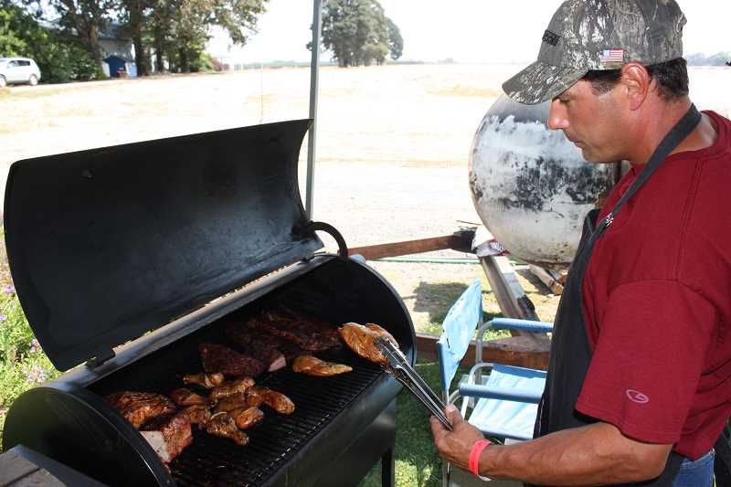 by: FILE PHOTO - Teams at the sixth annual Woodburn Firehouse Cook-off will compete for best in beef, pork and chicken.
