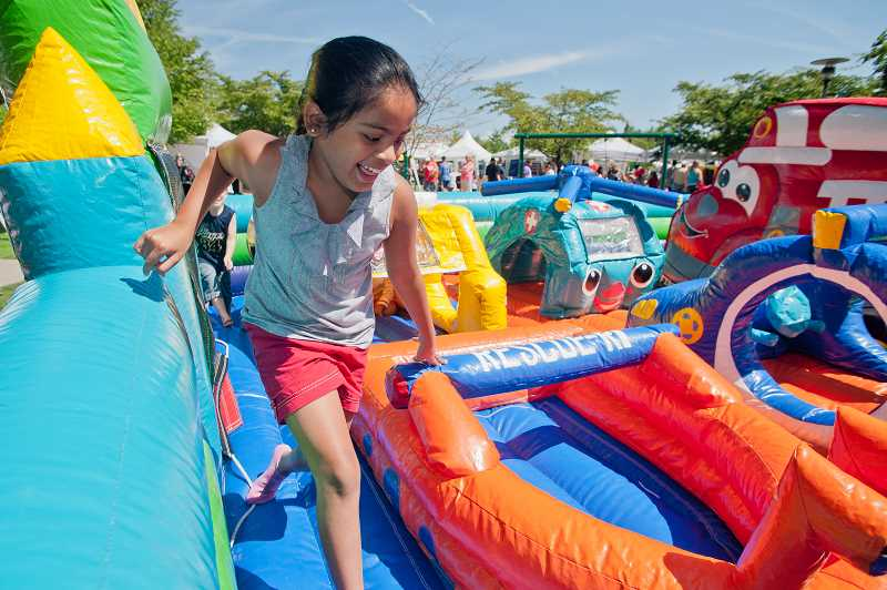 by: JOSH KULLA - Children of all ages enjoyed inflatable attractions like this one, as well as a wide range of fun sponsored by a large swath of Wilsonville businesses during Fun in the Park, held Saturday.