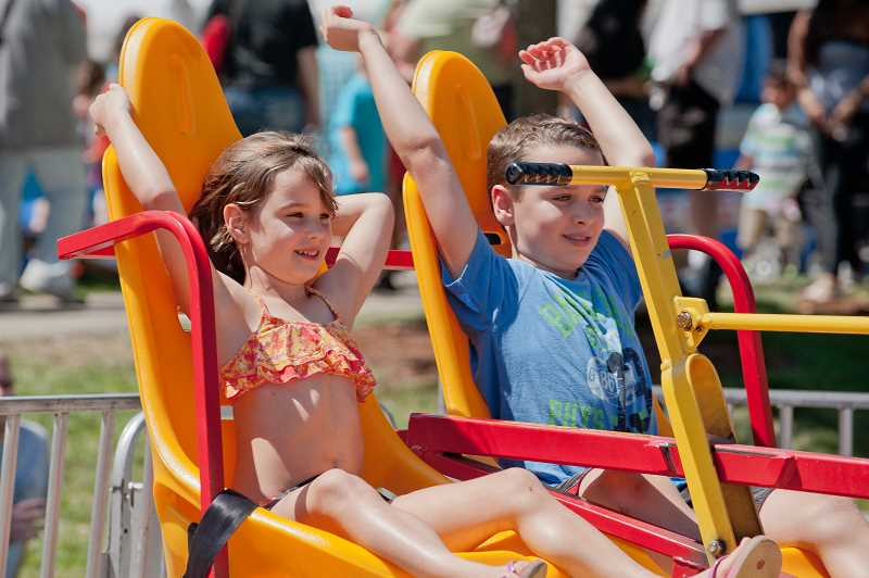 by: JOSH KULLA - A pair of riders feel the wind in their hair on one of the many attractions offered Saturday.