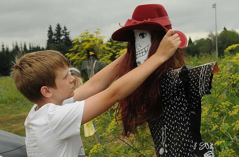 by: VERN UYETAKE - Connor Langley, 11, adjusts the hat of a scarecrow next to his familys garden plot.