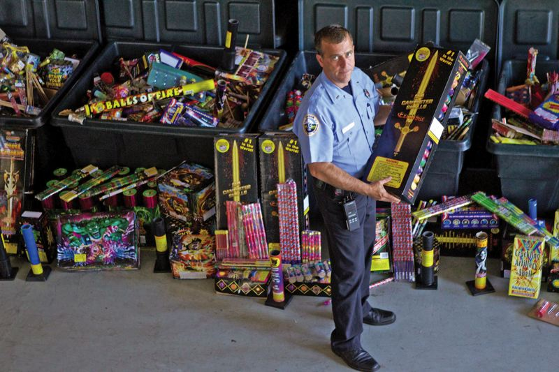 by: TRIBUNE PHOTO: JAIME VALDEZ - Portland Fire & Rescue Public Education Officer Michael Silva holds one of the 45,000 illegal fireworks that he collected that is stored in a warehouse. Silva says that the fireworks will be sent to an undisclosed location until November and will then be destroyed.