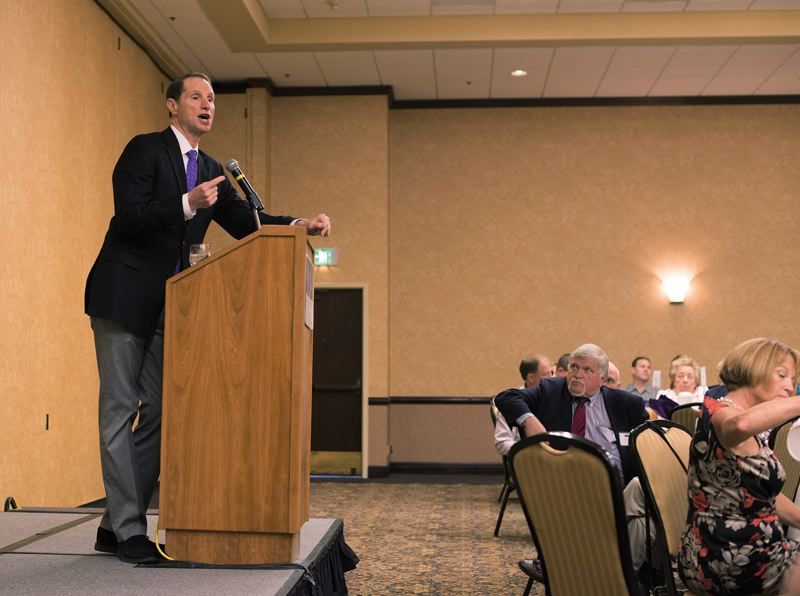 by: TRIBUNE PHOTO: CHASE ALLGOOD - Metro President Tom Hughes watches intently as Oregon U.S. Sen. Ron Wyden addresses the Westside Economic Alliance.