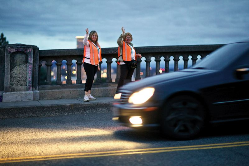 by: TRIBUNE PHOTOS: JAIME VALDEZ - Jan Schumacher and Jenny Duchene, volunteers with Friends of the Vista Bridge, wave to cars while patrolling the bridge.