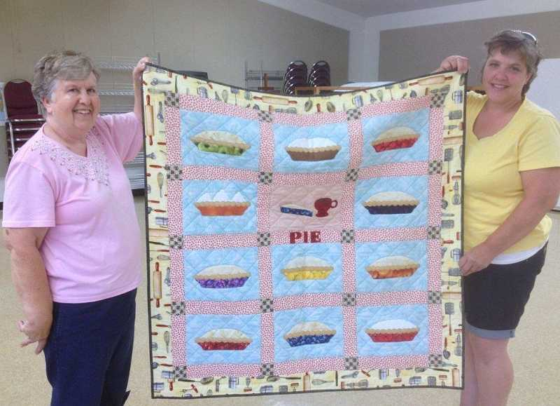 Pie booth chairwoman, Bobbie Knapp, and purchasing chairwoman, Jill Kahle, display the CUMC pie quilt.