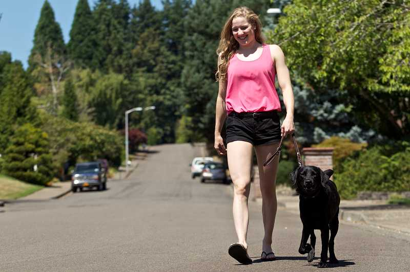 by: TIMES PHOTO: JAIME VALDEZ - Blaise Wittenauer-Lee of Cedar Mill walks Alberta, a black Labrador, which her family initially raised as a guide dog but now is the family pet. Wittenauer-Lee recently was awarded a $600 scholarship for her scholastic achievements and her commitment to community service with Guide Dogs for the Blind.