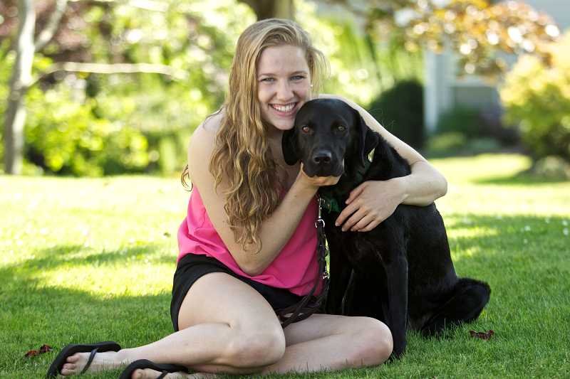 by: TIMES PHOTO: JAIME VALDEZ - Blaise Wittenauer-Lee of Cedar Mill hugs Alberta, a black Labrador. Wittenauer-Lee and her family have helped train several puppies for Guide Dogs for the Blind.