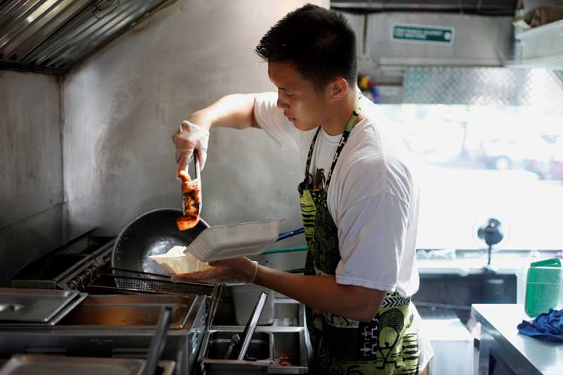 TIMES PHOTO: JONATHAN HOUSE - Chef Kalei Miller fries chicken at the 808 Grinds food truck on Southwest 68th Parkway. The truck regularly stops outside the Clear Channel building in Tigard on Tuesday afternoons.