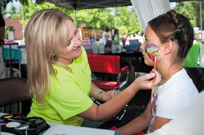 by: JOSH KULLA - Lynne Tucker paints a butterfly on the face of a girl during the Fun in the Park festival. The booth was sponsored by St. Francis of Assisi Church in Wilsonville.