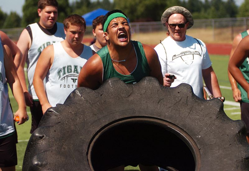 by: DAN BROOD - POWER -- Janak Ward, a Tigard High School senior-to-be, gives it everything he has in the tire flip competition at the Metro Area Lineman Challenge, which was held at Tualatin High School.