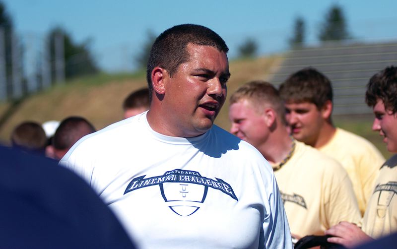 by: DAN BROOD - IN CHARGE -- Tualatin High assistant football coach Ian Reynoso, founder of the Metro Area Lineman challenge, talks to the competitors during this year's event.