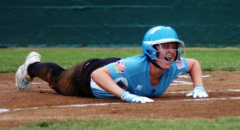 by: DAN BROOD - WORLD SERIES SMILE -- Tualatin City's Noelle Sawyer flashes a big smile after sliding safely to home plate in the second inning of the team's 7-1 World Series win over Italy.