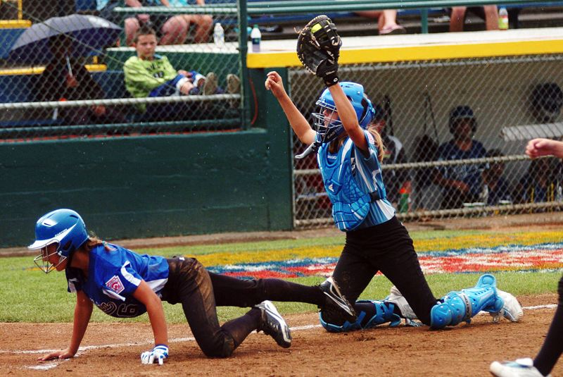 by: DAN BROOD - BIG PLAY -- Tualatin City catcher Ella Hillier (right) holds up the ball after tagging out Italy's Chiara Marazzi in a rundown during Saturday's game at the Little League Softball World Series.
