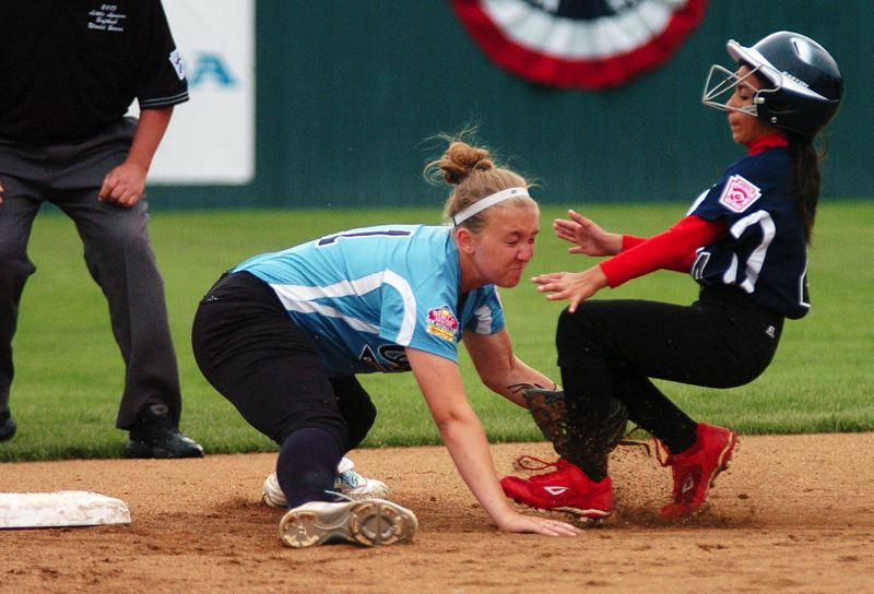 by: DAN BROOD - COLLISION COURSE -- Tualatin City shortstop Noelle Sawyer (left) is about to tag out Puerto Rico's Omaris Torres on a stolen base attempt during Sunday's game at the Little League Softball World Series.