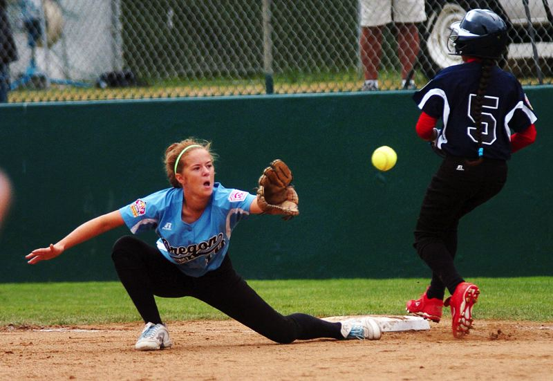 by: DAN BROOD - CLOSE PLAY -- Tualatin City first baseman Lindsay Stadick (left) stretches for the ball as Puerto Rico's Alejandra Rodriguez runs to the bag in Sunday's game at the Little League Softball World Series.