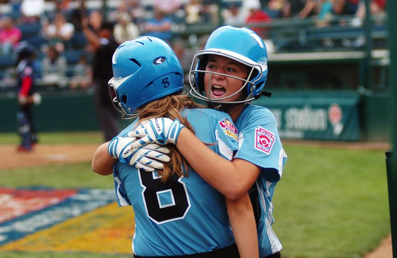 by: DAN BROOD - HAPPY HUG -- Tualatin City's Lindsay Stadick (left) hugs Ella Hillier after they both scored in the fifth inning in Sunday's Little League Softball World Series. Tualatin City rallied to score a 6-5 win over Puerto Rico.