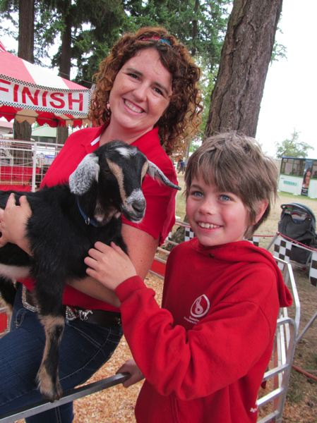 by: PHOTO BY ELLEN SPITALERI - Emilie Owen lets Ethan, 9, pet one of her goats at the Clackamas County Fair last year.