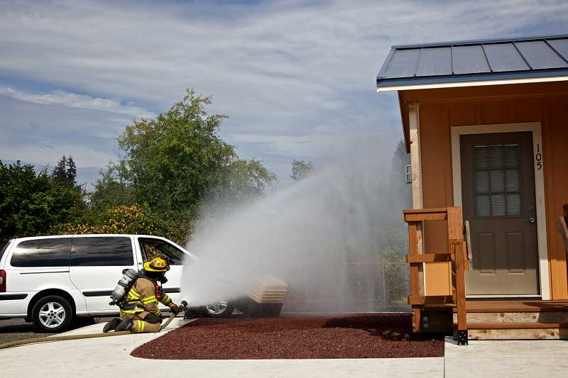 by: TIMES PHOTOS: JAIME VALDEZ - A Tualatin Valley Fire & Rescue firefighter sprays water on an above-ground service regulator during a training exercise at Training Town, which is part of NW Natural's Sherwood Operations and Training Center.