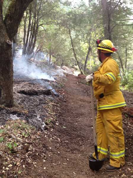 by: HUBBARD FIRE DISTRICT - Jared Lynch, a volunteer firefighter with the Hubbard Fire District, watches over the fire line near Wolf Creek.