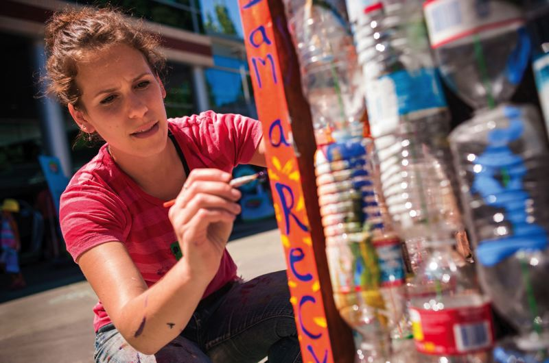 by: PAMPLIN MEDIA GROUP: NICK FOCHTMAN - Trash For Peace founder Laura Kutner puts the finishing touches on one of the nonprofits signature trash bins.
